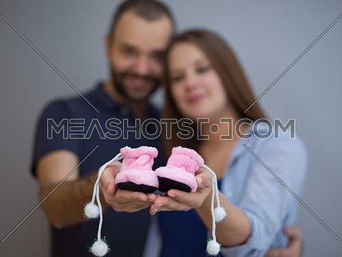 young  pregnant couple holding newborn baby shoes isolated on white background in family and parenthood concept