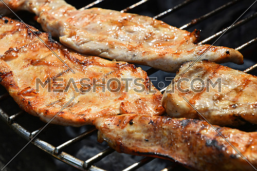 Chicken or turkey meat barbecue steak ready cooked grilled on bbq smoke grill, close up