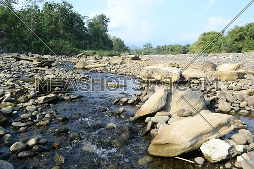 Bogowonto River, Purworejo / Indonesia - July 22, 2020: Bogowonto River With Water Flowing Through Many Rocks During the Day