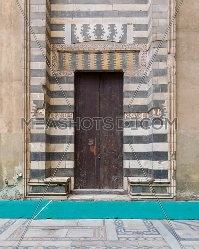 Wooden aged door surrounded by striped black and white marble decorations and stone wall at the courtyard of Sultan Hassan Mosque, Cairo, Egypt
