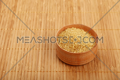 Small wooden round bowl full of brown cane sugar on bamboo mat background