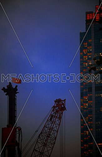 construction cranes on night ove a blue sky