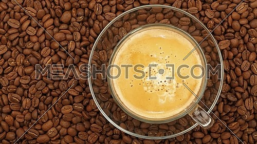 Close up one glass cup full of latte coffee with milk on transparent saucer, over background of roasted coffee beans with slow motion animated cinemag