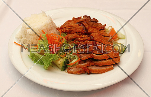 Peking duck Chop Suey with steamed rice and fresh vegetable salad on white plate, the meal of Chinese cuisine, close up, high angle view, personal perspective