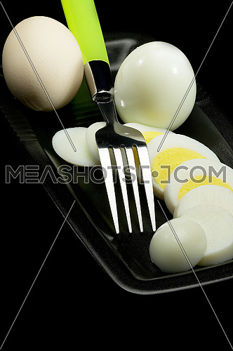 fresh boiled eggs one whole ,one peeled and another sliced on a black plate with fork