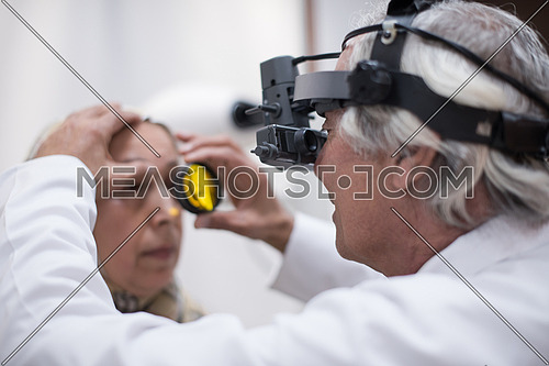 Middle Eastern Ophthalmologist examing cornea of senior woman with slit lamp in the modern clinic