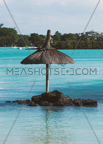 A sun umbrella in the middle of the water near the coast of the Indian Ocean, Mauritius