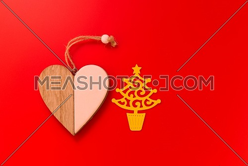 Wooden heart medallion of two separate sides placed next to a yellow paper Christmas tree cut out, isolated on bright red background with copy space