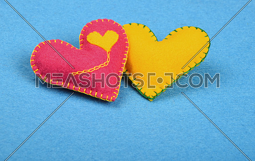 Felt craft and art, two handmade stitched toy hearts, pink and yellow together on blue background