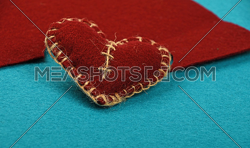 Felt craft and art, one handmade brown stitched toy heart with cut out on blue felt background, low angle view