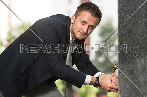 Young Businessman Refreshing Himself By Drinking Water