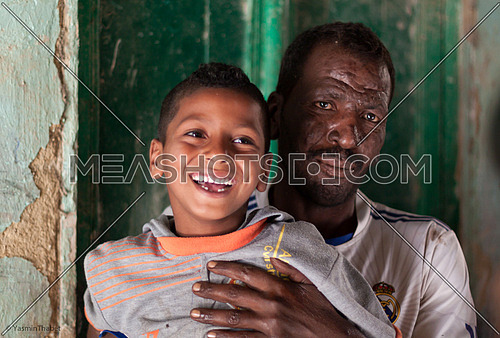 An Egyptian man is holding his son inside his home, Fayoum, Egypt