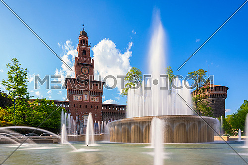 Main entrance to the Sforza Castle - Sforzesco castle and fountain in front of it,long exposure photo, sunny day and clouds in the sky,Milan, Italy