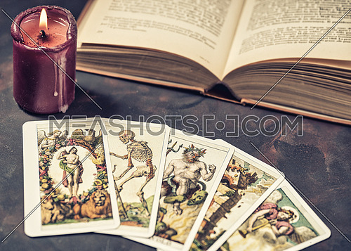 Tarot cards with candlelight and book on the darkness background,Halloween and future reading concept.