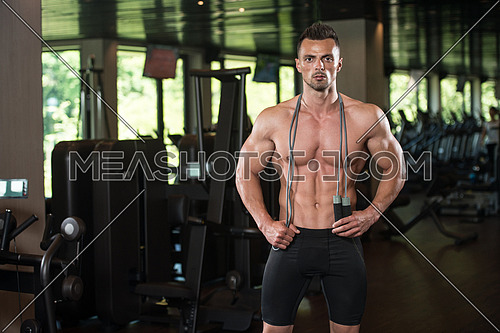 Portrait Of A Physically Fit Man Posing With Jumping Rope In Modern Fitness Center Gym