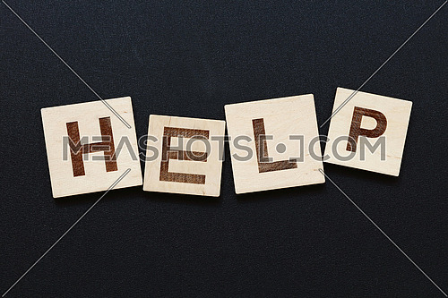 Close up word HELP on wooden letter signs over black board background