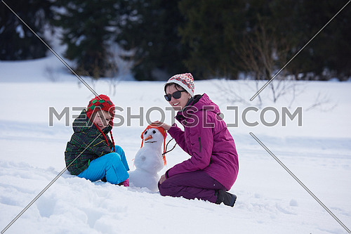 happy young  family playing in fresh snow and building snowman at beautiful sunny winter day outdoor in nature
