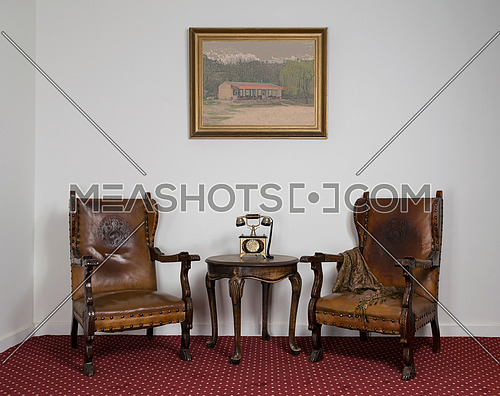 Composition of two wooden armchairs, old telephone set on small round coffee table and framed painting on red carpet and white wall
