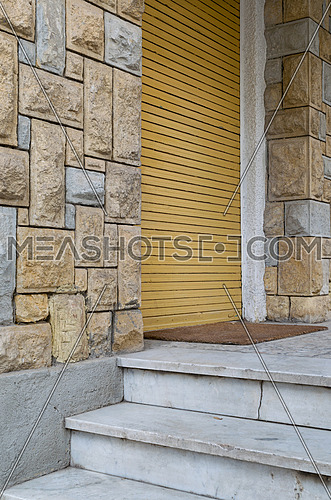 Angled view of stone bricks colored wall, three white marble steps, and closed yellow vertical roller door