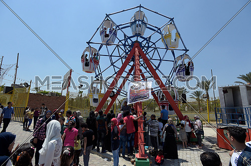 Some young Egyptian people waiting turn to ride a small ferris wheel in amusement park