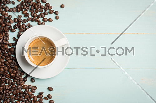 White cup of coffee and coffee bean on green background. Copy space,view from above