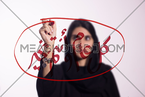 "Arabian middle eastern business woman writing with a marker on virtual screen in arabic كل عام و انتم بخير suggesting season greeting ""happy new year"" ""Happy Birthday"" isolated on white background"