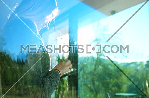 close up shot through window for a Woman using tablet at home by the window