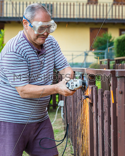 In the picture a older man at work using a sander.