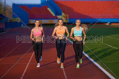 athlete woman group  running on athletics race track on soccer stadium and representing competition and leadership concept in sport