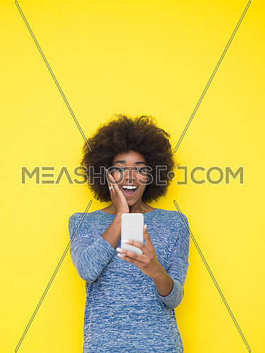 Young Happy African American Woman Using mobile phone  Isolated on a yellow background