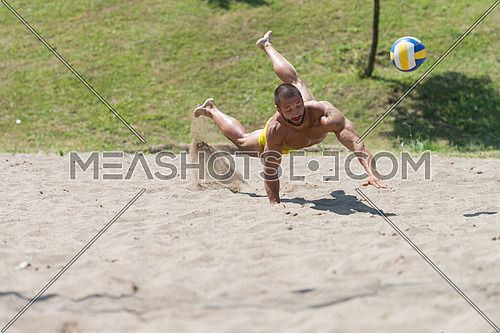 Muscular Young Man Playing Beach Volleyball Diving After The Ball