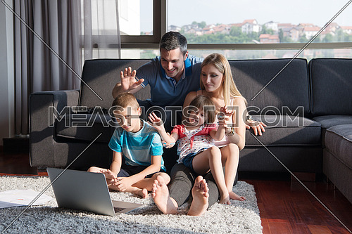 Happy Young Family Playing Together with laptop computer at home sitting on the sofa