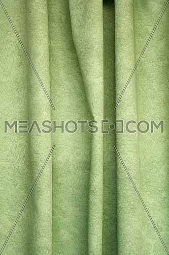 Heavy light green pleated felt textile curtain background with portiere drape folds, side view close up