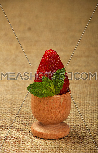 One big red mellow strawberry and green fresh mint leaves in wooden eggcup holder on natural burlap jute canvas background