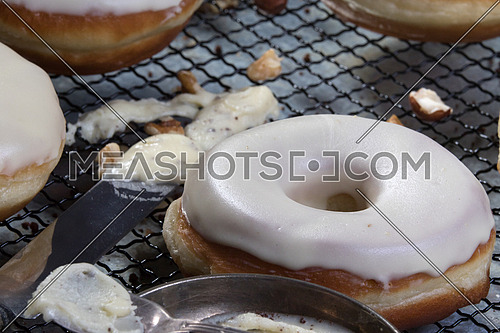 top side view  of white glazed donuts with walnuts aside and white chocolate paste