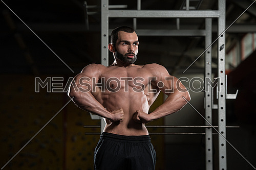 Young Man Standing Strong In The Gym And Flexing Front Lat Spread Pose - Muscular Athletic Bodybuilder Fitness Model Posing Exercises