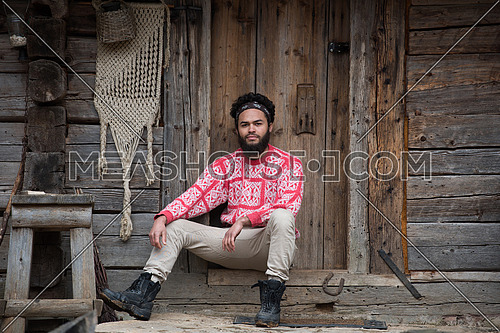 portrait of young hipster,  man with beard in front of old vintage wooden house
