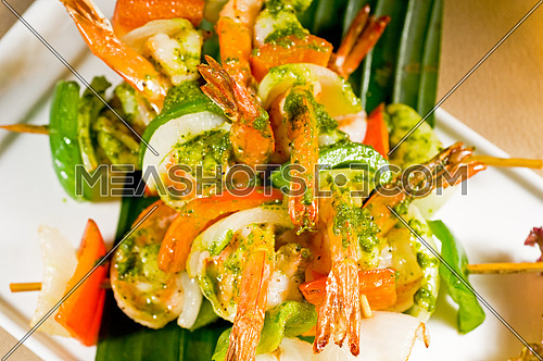 fresh and colorfull grilled shrimps and vegetables skewers on a palm leaf ,thai style