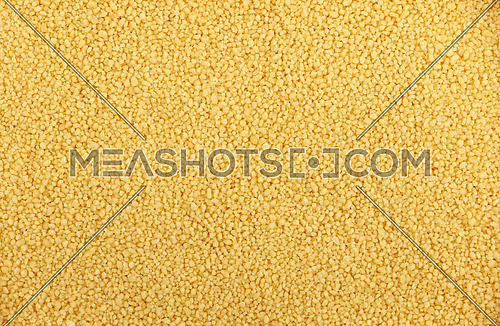 Yellow traditional wheat couscous close up pattern background, elevated top view
