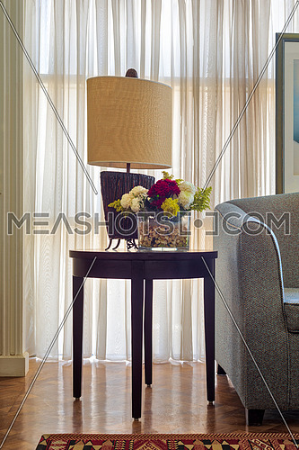 Table lamp and colorful flowers planter on small dark brown wooden table on background of big window with white sheer curtains and grey armchair