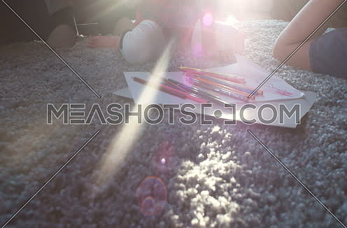Parents and kids coloring together at home in living room and sun flares from window
