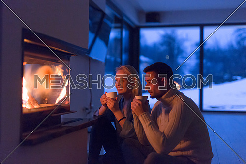 Young romantic couple sitting on the floor in front of fireplace,talking and drinking tea on cold winter night at home