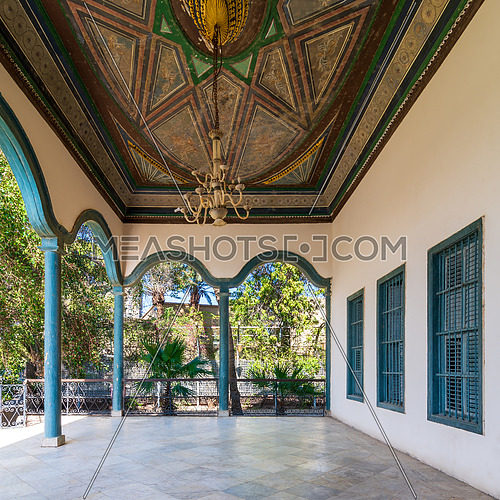 Covered terrace with decorated painted ceiling, green stone pillars, and marble floor fenced with metal forged fence and surrounded with green trees in sunny summer day