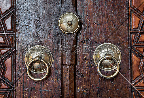Closeup of two antique copper ornate door knockers over an aged wooden door, Suleymaniye Mosque, Istanbul, Turkey