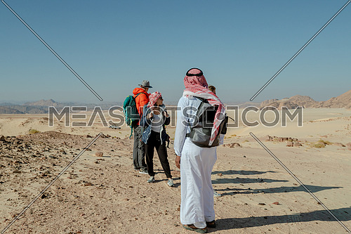 Group of tourists walking on sands with bedouin guide while exploring Sinai Trail in Ain Hodouda by day.