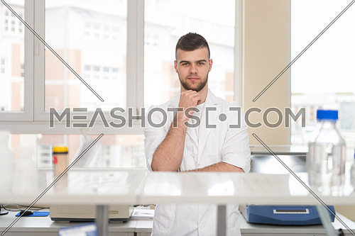 Portrait Of A Caucasian Student In A Chemistry Lab Smiling And Looking In The Camera With Hands Folded