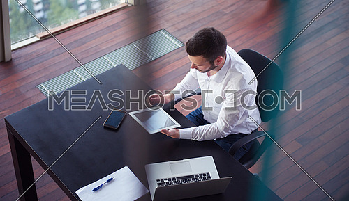 top view of happy young business man,  work tablet and laptop and relax at modern bright office interior, successful hipster with beard at workplace