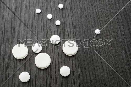 Some round white pills of different size