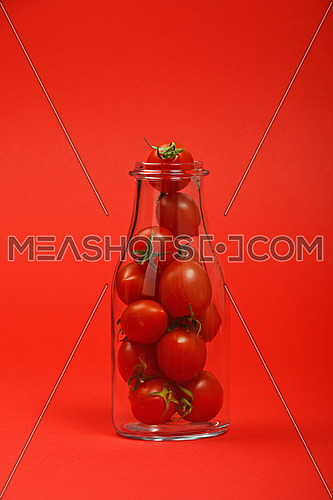 Big glass bottle full of cherry tomatoes over red background as symbol of fresh natural organic juice or ketchup