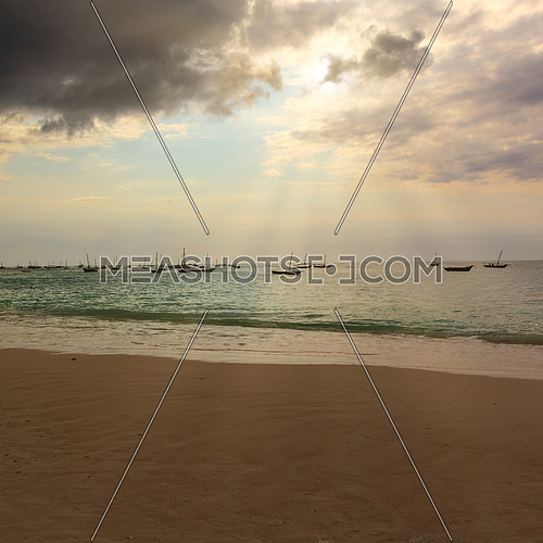 Several fishing boats silhouette anchored out in the ocean off the coast of Zanzibar, at sunset with sunbeams.